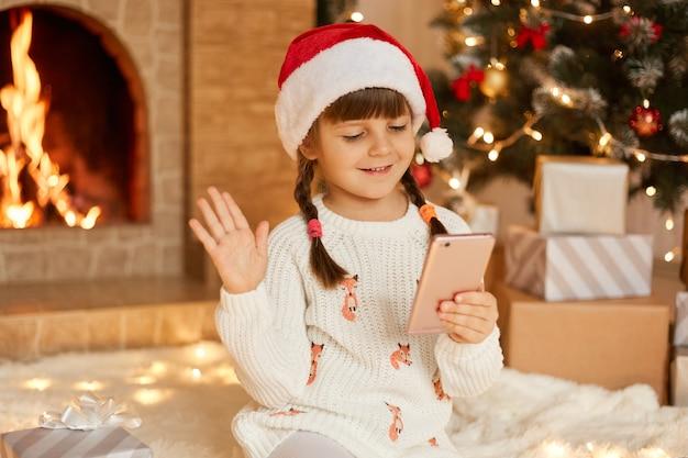 Natal online, parabéns de casa, menina sorridente usando telefone inteligente para chamada de vídeo. criança fala com amigos e pais, acena as mãos para cumprimentar, usando chapéu de papai noel, posa na sala festiva.