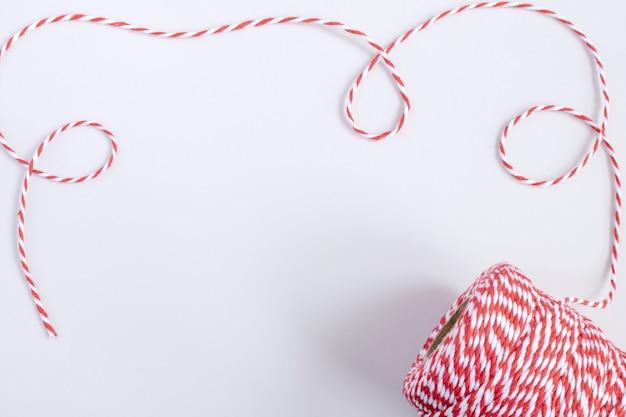 Natal ou ano novo conceito - torcido cabo vermelho e branco isolado, branco