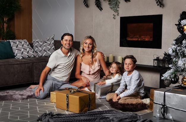 Natal ou ano novo família abrir presentes presentes mamãe, papai e crianças sorrindo boas festas