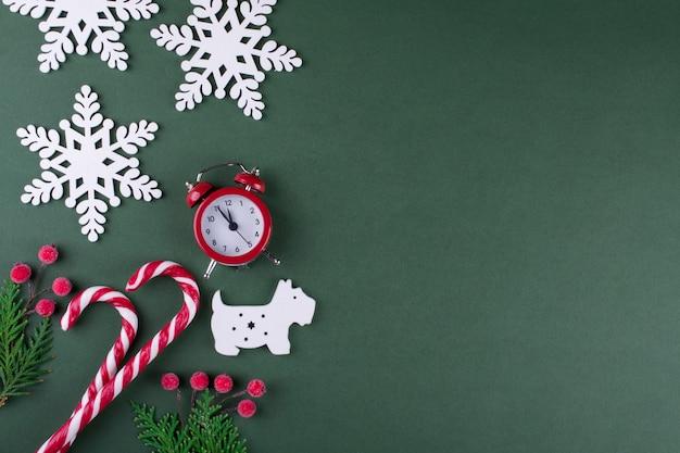 Natal ou ano novo plano leigos com figura de madeira de cachorro e flocos de neve, pinheiros, bastões de doces e relógio vermelho. sobre fundo verde.