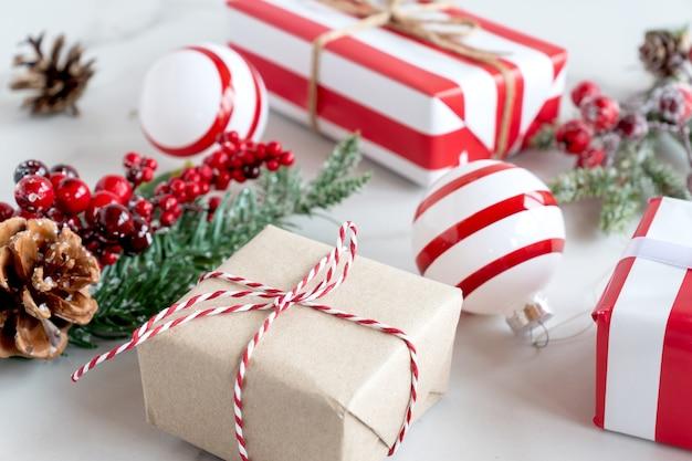 Natal ou ano novo presentes de férias embrulhados em artesanato e papel listrado com fita. caixas surpresa de presente artesanal com decorações diy no fundo da mesa de mármore.