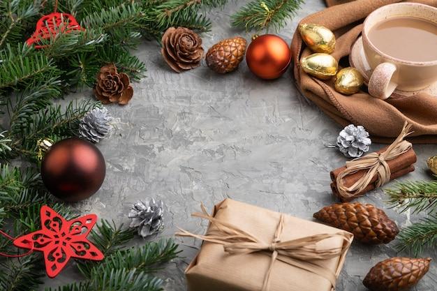 Natal ou composição. decorações, cones, canela, ramos de abeto e abeto, xícara de café, lenço de lã em concreto cinza.