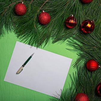 Natal plana leigos pedaço de papel e caneta encontra-se sobre uma mesa verde clara, decorada com galhos de cedro com bolas vermelhas de ano novo de cores diferentes.