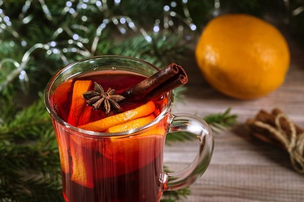 Natal quente com vinho e tangerinas em um fundo de madeira.