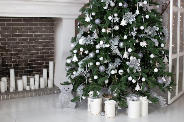 Natal! sala de estar decorada com lareira com linda árvore de natal e bolas. caixas de presente de natal no chão perto de abeto na sala.