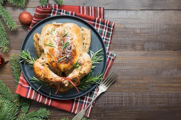 Natal tradicional frango assado com especiarias e alecrim na mesa de madeira. vista do topo.