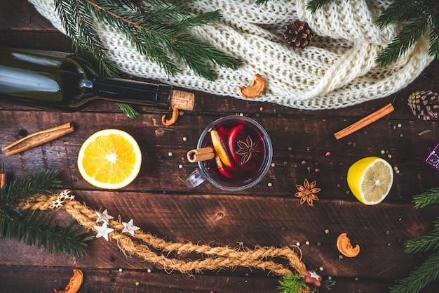 Natal, vinho quente quente em um copo com especiarias e frutas cítricas. uma noite de inverno aconchegante. bebidas de inverno. vista plana leiga, superior.