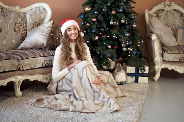Natal. woaman vestiu suéter branco com chapéu de papai noel e jeans sentado no chão perto da árvore de natal com caixa de presente