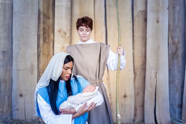 Natividade em versão transgênero representando uma cena em que maria segura jesus nos braços ao lado de josé