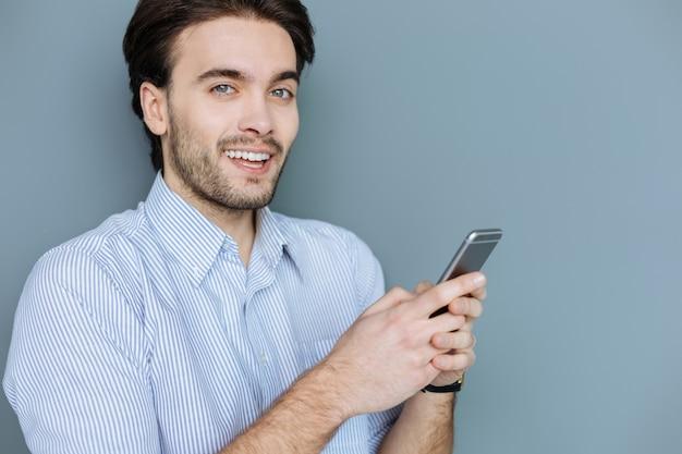 Nativo digital. homem barbudo atraente e positivo segurando seu smartphone e sorrindo para você enquanto conversa online