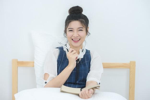 Natural alegre mulher asiática sentada na cama no quarto brilhante e escrevendo seu diário
