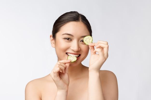 Natural caseiro pepino fresco almofadas faciais máscaras faciais mulher asiática segurando almofadas de pepino e sorriso relaxar com natural caseiro
