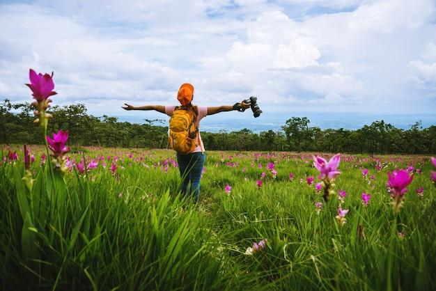Natureza asiática do curso da mulher viajar relaxar. campo de flor dos sessilis do pepino da fotografia.
