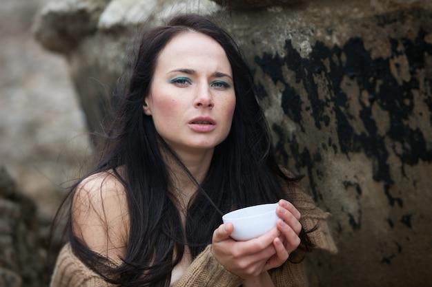 Natureza, beleza, juventude e conceito de estilo de vida saudável. jovem linda com um suéter de tricô no fundo de um velho muro de concreto, bebendo chá em uma xícara branca