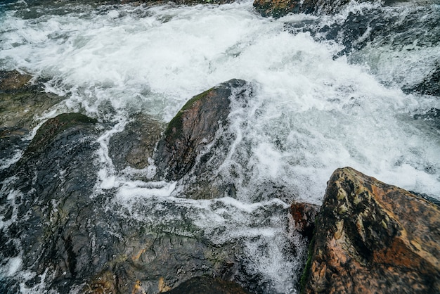 Natureza de quadro completo com pedregulhos no riffle de água do rio da montanha. fluxo de água poderosa do riacho de montanha. pano de fundo texturizado de fluxo rápido de riacho de montanha com corredeiras. close-up de pedras grandes