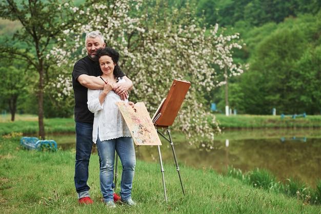Natureza deslumbrante. casal maduro tem dias de lazer e trabalhando na pintura juntos no parque
