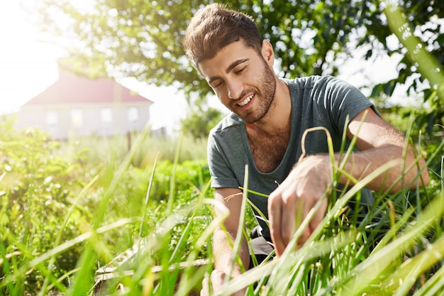 Natureza e meio ambiente. jovem jardineiro barbudo de pele escura, passando algum tempo no jardim perto de casa de campo. homem cortando folhas e aproveitando o clima quente do verão na sombra das árvores