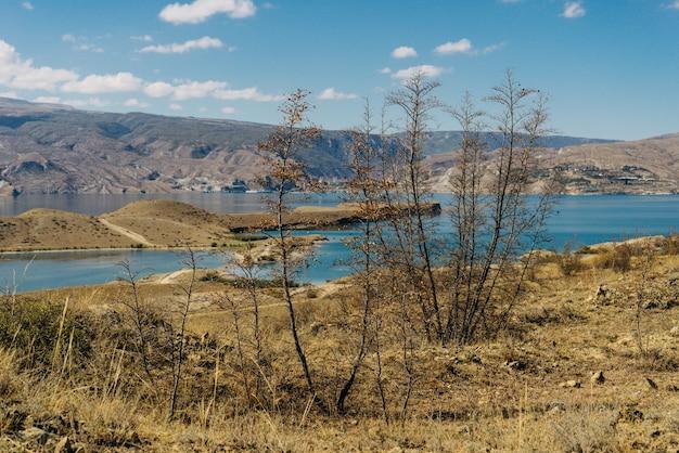 Natureza inspiradora, água azul, encostas e montanhas ao sol