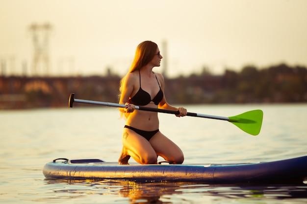 Natureza. jovem mulher sentada na prancha de remo, sup. vida ativa, esporte, conceito de atividade de lazer