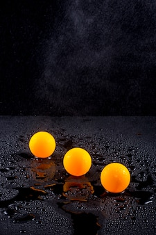 Natureza morta abstrata com três bolas de laranja sob irrigação por gotejamento com água