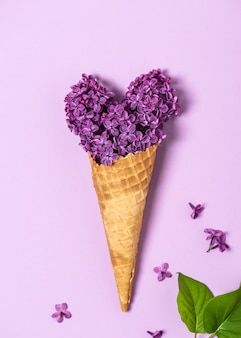 Natureza morta abstrata de uma casquinha de waffle de sorvete com flores lilases comestíveis em forma de coração
