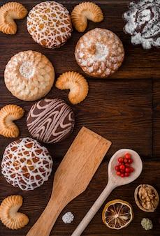 Natureza morta aconchegante com conjunto de padaria: biscoitos caseiros, bolos, nozes, amora na textura de madeira escura.