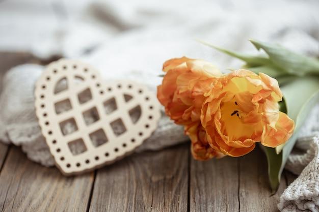 Natureza-morta aconchegante com um coração decorativo e um buquê de flores de perto