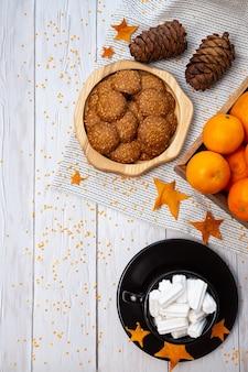 Natureza-morta aconchegante de inverno com biscoitos de tangerina, pinhas e uma xícara de marshmallows