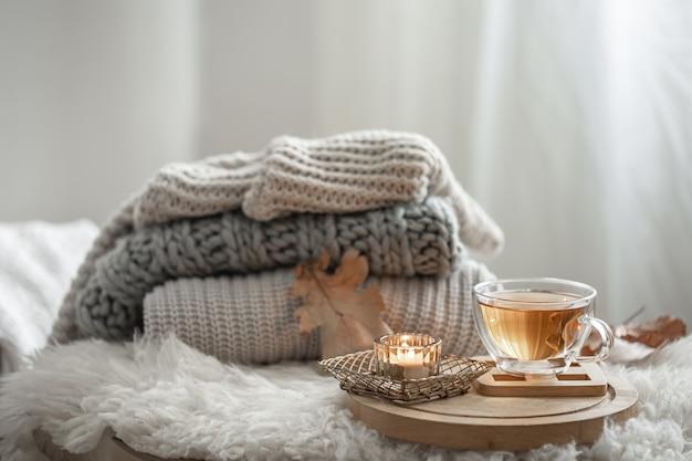 Natureza morta caseira com camisolas de malha e uma xícara de chá em um fundo desfocado.
