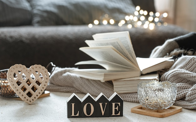 Natureza morta com a palavra de madeira amor, livros e itens aconchegantes em um fundo desfocado com boke.