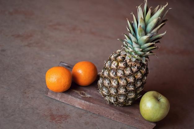 Natureza morta com abacaxi, laranja e maçã em fundo de madeira