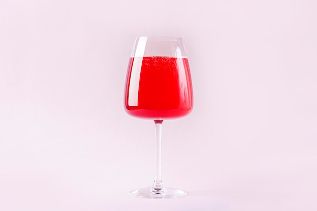 Natureza morta com bebida alcoólica refrescante de verão vermelha com morango em uma taça de vinho isolada no fundo rosa