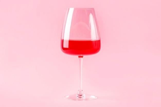 Natureza morta com bebida alcoólica refrescante de verão vermelha com morango na taça de vinho isolada no fundo rosa