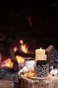 Natureza morta com bebidas quentes, velas e decoração no contexto de uma lareira.