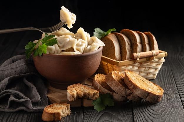 Natureza morta com bolinhos quentes em uma tigela de barro e pão de centeio torrado