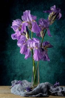 Natureza morta com buquê de íris roxas dentro de um vaso de vidro sobre uma mesa rústica com musselina no azul