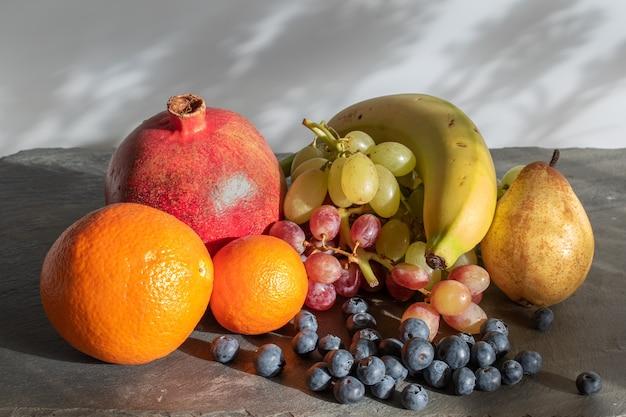 Natureza morta com cacho de uvas, laranjas, romã, banana e mirtilos