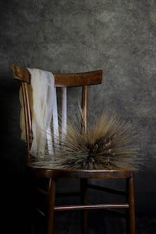 Natureza morta com cadeira vintage e molho de espigas de trigo