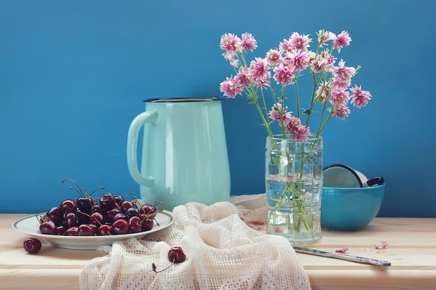 Natureza morta com cerejas e um buquê de aquilegia na mesa. frutos maduros em um prato.