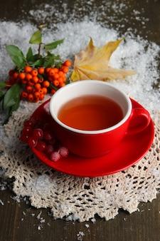 Natureza morta com chá viburno laranja na xícara, frutas vermelhas e neve, em fundo de madeira