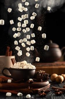Natureza morta com chocolate quente e marshmallows. marshmallow e canela em pó caem de cima. o vapor quente sobe da caneca
