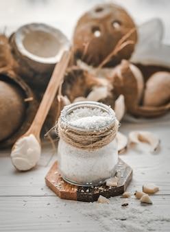 Natureza morta com coco e flocos de coco em colheres de madeira e jarra de vidro com fundo de madeira
