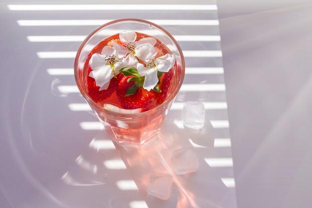 Natureza morta com copo de sangria de morango refrescante com espumante, morango, cubos de gelo