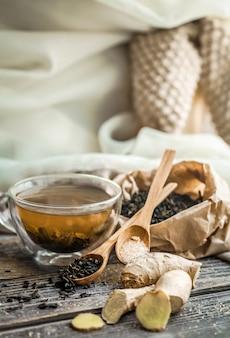 Natureza morta com copo transparente de chá na mesa de madeira