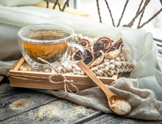 Natureza morta com copo transparente de chá no fundo de madeira