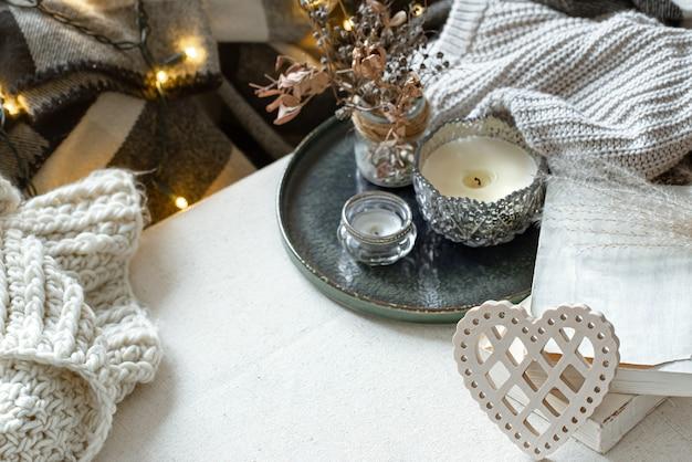 Natureza morta com coração decorativo, livros e velas em castiçais. o conceito de dia dos namorados e a decoração da casa.