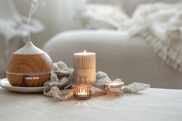 Natureza morta com difusor de aromas para hidratar o ar e acender velas.