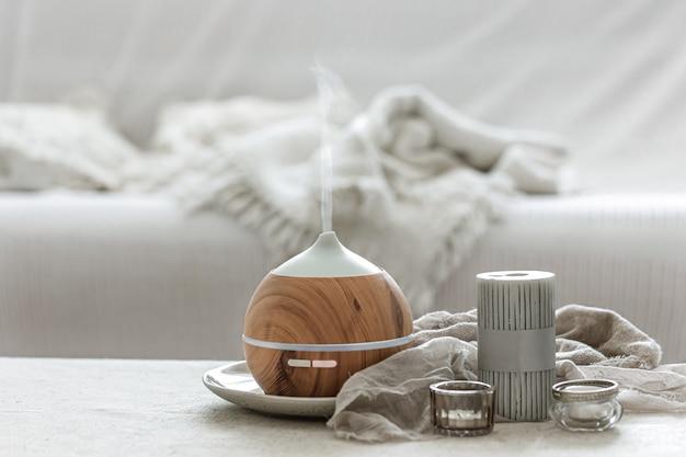 Natureza morta com difusor de aromas para humedecer o ar e pormenores de decoração interior ao estilo escandinavo.