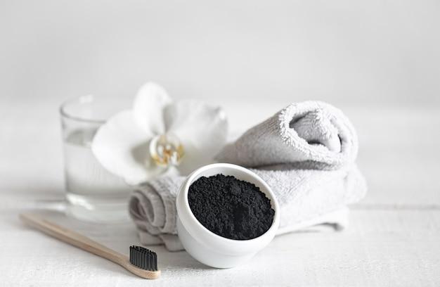 Natureza morta com escova de dentes de madeira orgânica com um copo de água e pó clareador natural dos dentes. higiene bucal e atendimento odontológico.