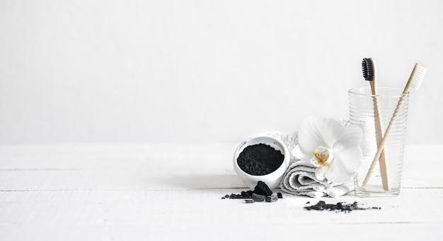 Natureza morta com escovas de bambu orgânico e pó de carvão ativado e uma flor de orquídea como elemento decorativo